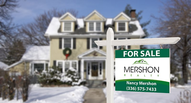 Mershon Realty sign in front of snow covered house